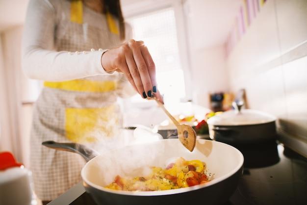 In de keuken wordt door een jonge vrouw een gezonde en voedzame maaltijd voor het gezin bereid.