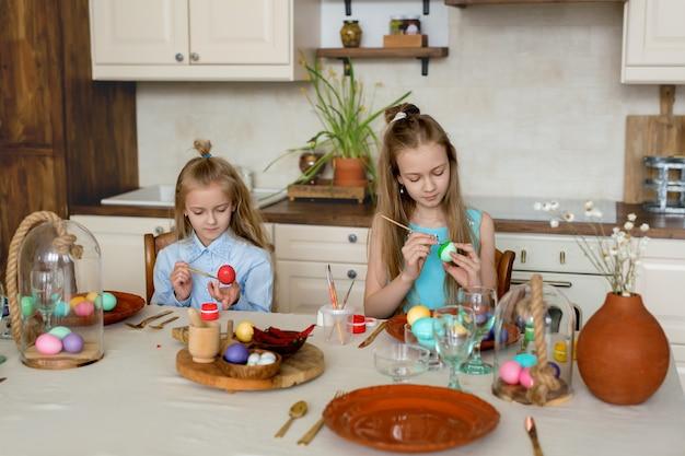 In de keuken zijn twee zusjes bezig met het kleuren van paaseieren