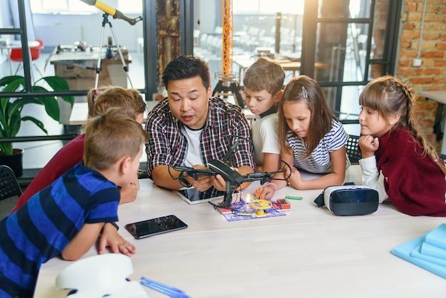 In de les natuurkunde en mechanica demonstreert een jonge aziatische leraar quadcopter voor blanke leerlingen in de klas in een moderne slimme school. wetenschap, drone, techniek en toekomstig concept.