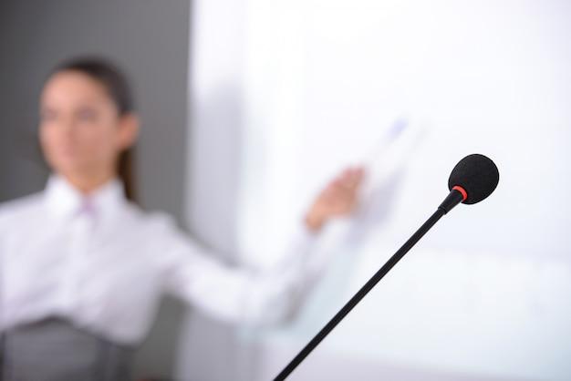In de nabije weergave van de microfoon in het achterste luidspreker meisje.