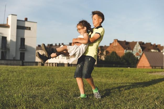 In de natuur in de zomer rolt een broer zijn zus in zijn armen. zonnige dag