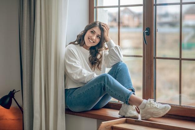 In de ochtend. mooie jonge langharige vrouw in een witte blouse die bij het raam zit en er attent uitziet