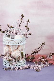 In de oude decoratieve kooi zitten takken van bloeiende kers (verticale lijst)