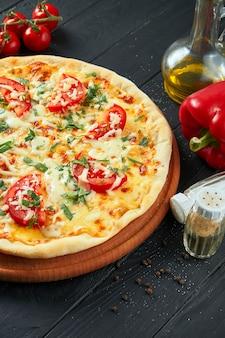 In de oven gebakken pizza margherita met tomaten, mozzarella kaas en rode saus op een houten oppervlak in een compositie met ingrediënten