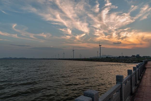 In de schemering, de roze wolken en windmolens op het strand