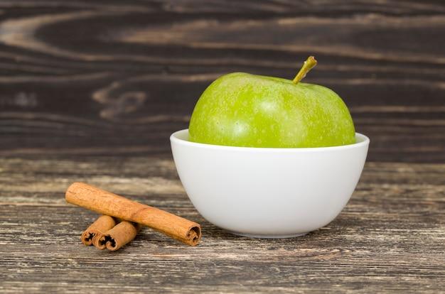 In de schil van een groene appel en geurige kaneel op een houten snijplank