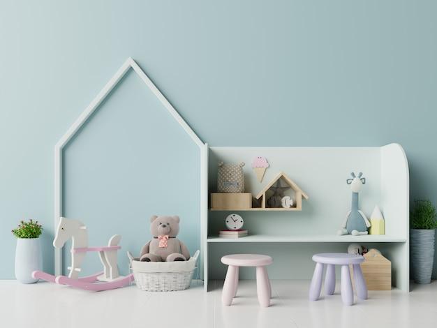 In de speelkamer van kinderen met tent en tafel zitten pop op lege blauwe muur.