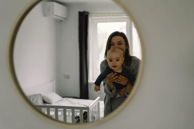 In de spiegel laten zien hoe een moeder met haar kind speelt. moeder van een zogende baby. gelukkig moederschap. het gezin is thuis. portret van een gelukkige moeder en kind.