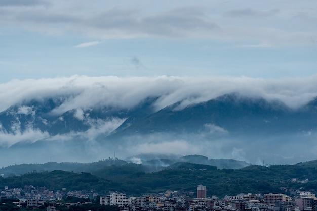 In de stad na de regen zijn er wolken in de bergen in de verte