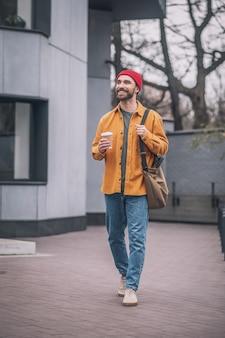In de straat. man in een oranje jas die over straat loopt
