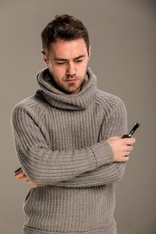 In de studio op een grijze achtergrond staat een man in een grijze trui peinzend, kruist zijn armen op borsthoogte en houdt een pijp en lucifers in zijn handen.