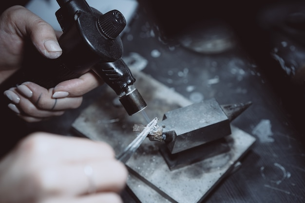 In de werkplaats is een vrouwelijke juwelier bezig met het solderen van sieraden