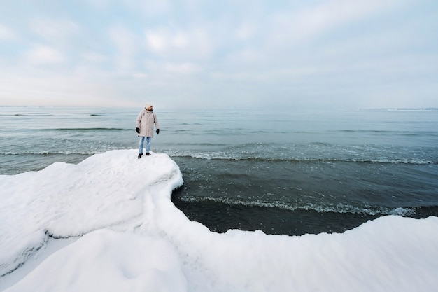 In de winter staat een toerist aan de oever van de oostzee. winter in de buurt van de baltische staten van tallinn. reizigers in de buurt van de zee in de winter
