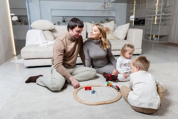 In de woonkamer zit een jong gezin met twee kleine kinderen op de grond. een fijne tijd samen. liefde en tederheid.