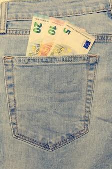 In de zak van blauwe jeans ingevoegd een aantal bankbiljetten in coupures van 5, 10, 20 euro