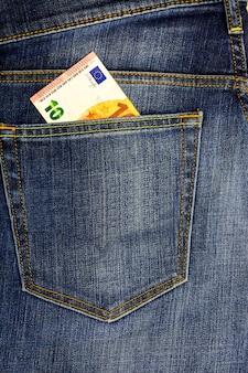 In de zak van donkere jeans geplaatst bankbiljet 10 euro