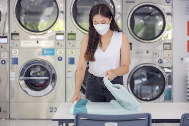 In de zelfbedieningswasserette met droogmachines op de achtergrond geniet een jonge vrouw van schoon gestreken kleding.