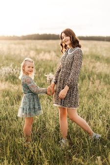 In de zomer wandelen oudere en jongere zussen samen in de natuur. zus knuffelt en kalmeert