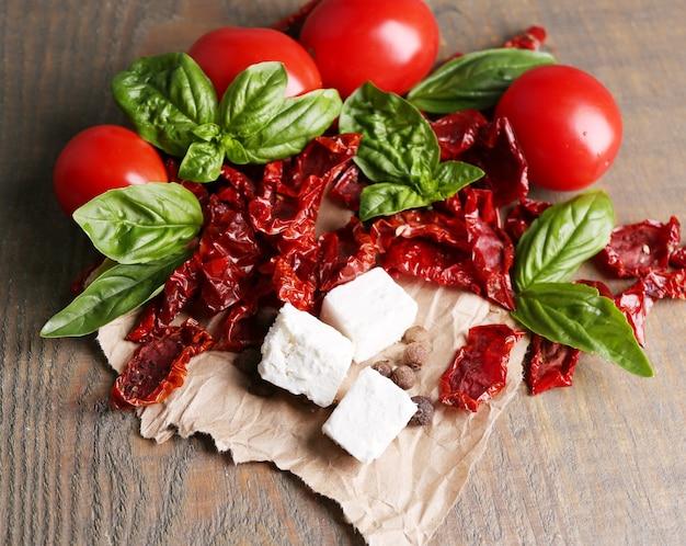 In de zon gedroogde en verse tomaten, basilicumbladeren en fetakaas op houten kleurenlijst