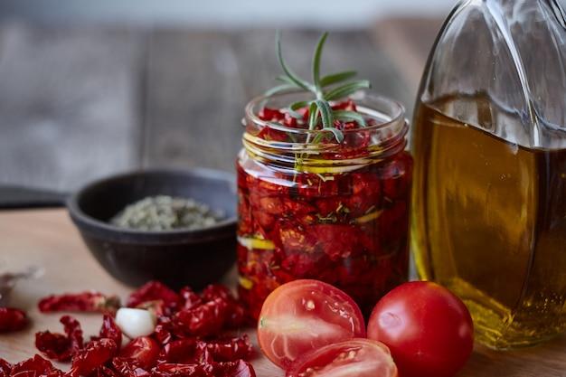 In de zon gedroogde tomaten met provençaalse kruiden, knoflook en olijfolie op een rustieke houten oppervlak, selectieve aandacht