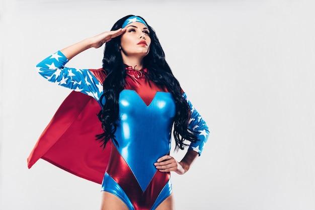 In dienst bij misdaadbestrijding. lage hoekmening van mooie jonge vrouw in superheld kostuum