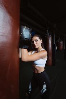 In dozen doende vrouw het stellen met bokszak, op donkere ruimte. sterk en onafhankelijk vrouwenconcept