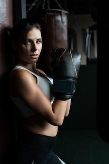 In dozen doende vrouw het stellen met bokszak. sterk en onafhankelijk vrouwenconcept