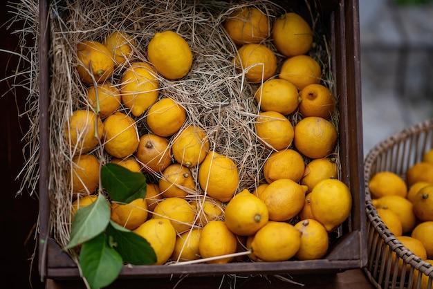 In een bruine houten kist zitten in stro geeloranje citroenen met groene twijgen. fris, levendig decor voor de aankleding van de festivalbeurs. natuurlijke vruchtensappen. kopieer ruimte