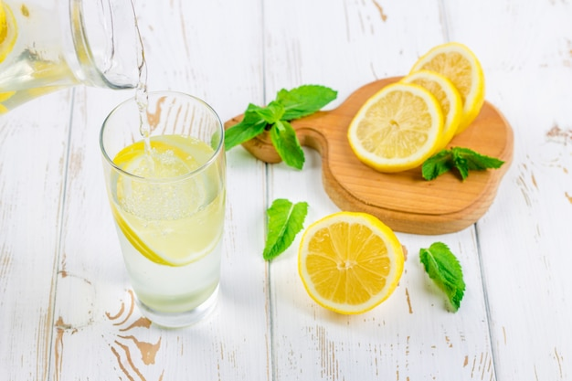 In een glasbeker, is een koude limonade gegoten kruik op witte houten die achtergrond door citroenen wordt omringd.