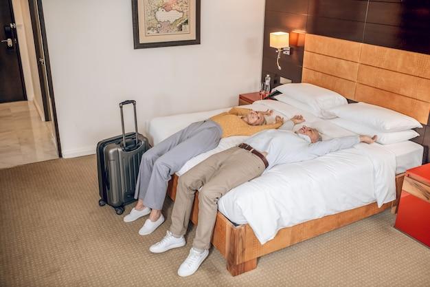 In een hotel. een stel dat op het bed in een hotelkamer ligt
