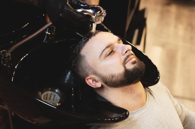 In een kapperszaak wast een man zijn haar. kapper wast zijn cliënt. was haar en baarden na het knippen. persoonlijke verzorging.