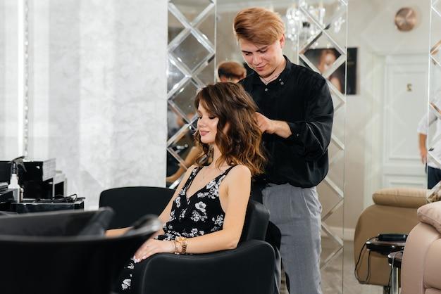 In een mooie, moderne schoonheidssalon maakt een professionele stylist een knipbeurt en een kapsel voor een jong meisje.