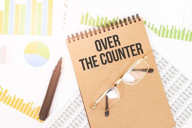 In een notitieboek in knutselkleuren staat een over the counter-inscriptie, naast potloden, brillen, grafieken en diagrammen.