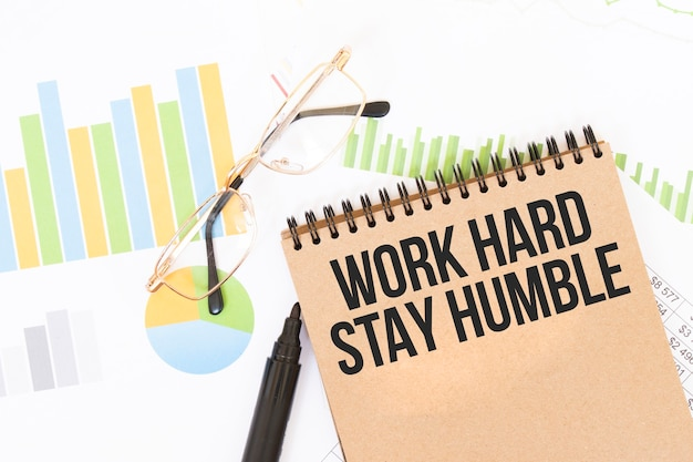 In een notitieboek in knutselkleuren staat een work hard stay humble-inscriptie, naast potloden, brillen, grafieken en diagrammen.