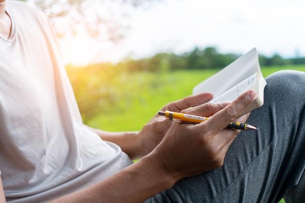 In een openbaar park schrijft een man met de hand in een klein wit memoblok om een aantekening te maken van iets dat hij niet wil vergeten of om een takenlijst te maken voor het toekomstige concept.