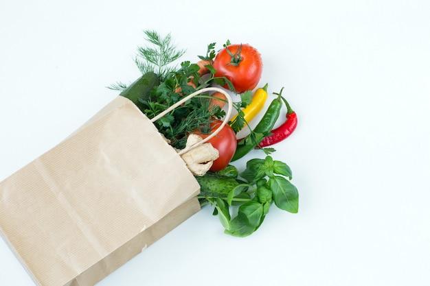 In een papieren zak verse groenten op een witte tafel