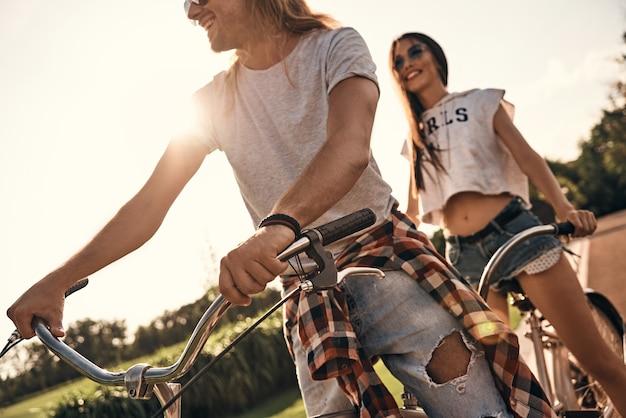 In een richting. mooie jonge paar in vrijetijdskleding samen fietsen terwijl ze zorgeloze tijd buitenshuis doorbrengen