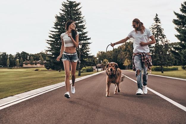 In een richting. volledige lengte van een mooi jong stel dat met hun hond rent terwijl ze tijd buitenshuis doorbrengen