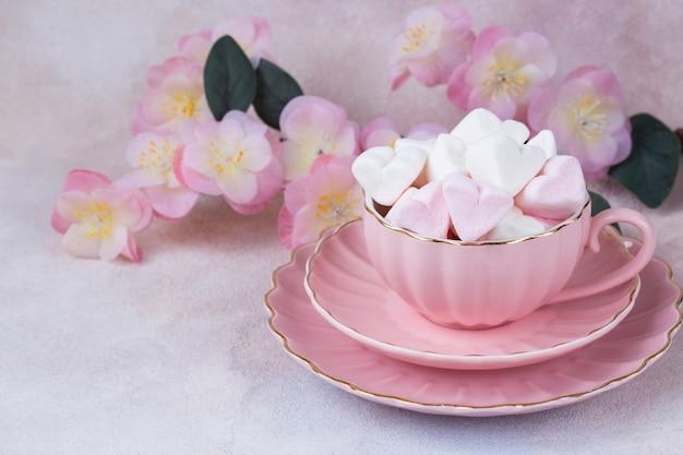 In een roze beker hartvormige marshmallows en roze bloemen