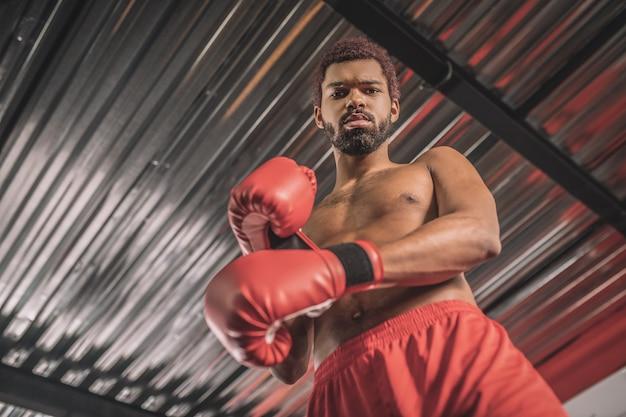 In een sportschool. donkere kickbokser in rode korte broek en rode bokshandschoenen