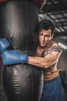 In een sportschool. gespierde man in blauwe korte broek die traint in een sportschool en er uitgeput uitziet
