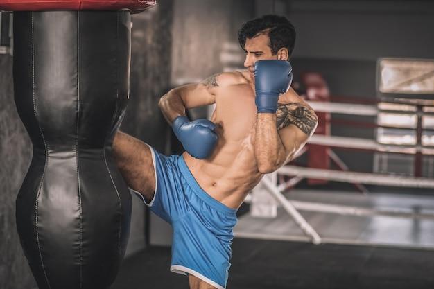In een sportschool. gespierde man in blauwe korte broek die traint in een sportschool en tegen de zandzak schopt