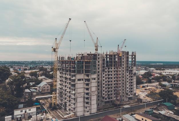 In een stadsdeel met laagbouwwoningen wordt een nieuw flatgebouw gebouwd. proces van huisvesting. problemen met de woningbouw in de stad. grootformaat geprefabriceerde blokken in woningbouw. een bevroren bouwproject.