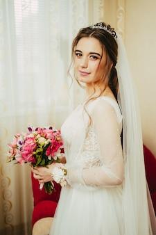 In een trouwjurk met het boeket in haar handen. bruid met boeket op witte achtergrond