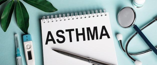 In een wit notitieboekje op een blauw oppervlak, naast een vel shefflers, een stethoscoop, een injectiespuit en een elektronische thermometer, wordt het woord astma geschreven. medisch concept