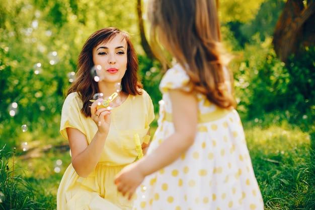 In een zomerpark bij groene bomen loopt mama in een gele jurk en haar kleine mooie meisje