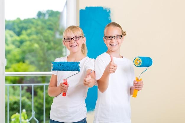 In family home schildert meisje met haar zus of vriendin met verfroller een muur in blauw