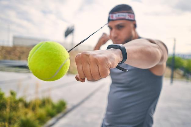 In focus slaat mannenhand met een smartwatch een gele tennisbal met zijn vuist