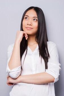 In gedachten verloren. doordachte jonge aziatische vrouw die de hand op de kin houdt en wegkijkt terwijl ze op een grijze achtergrond staat