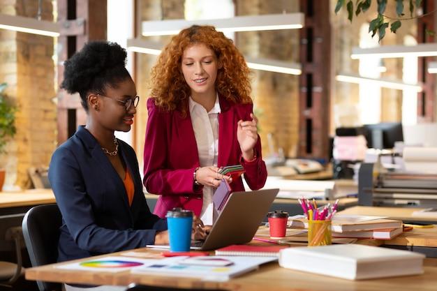In gesprek met baas. krullend roodharige assistent van interieurontwerper in gesprek met haar baas